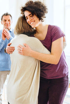 happy young lady hugging a woman